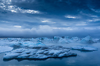 A wide angle landscape of icebergs floating in the Jokulsarlon glacial lagoon in Iceland