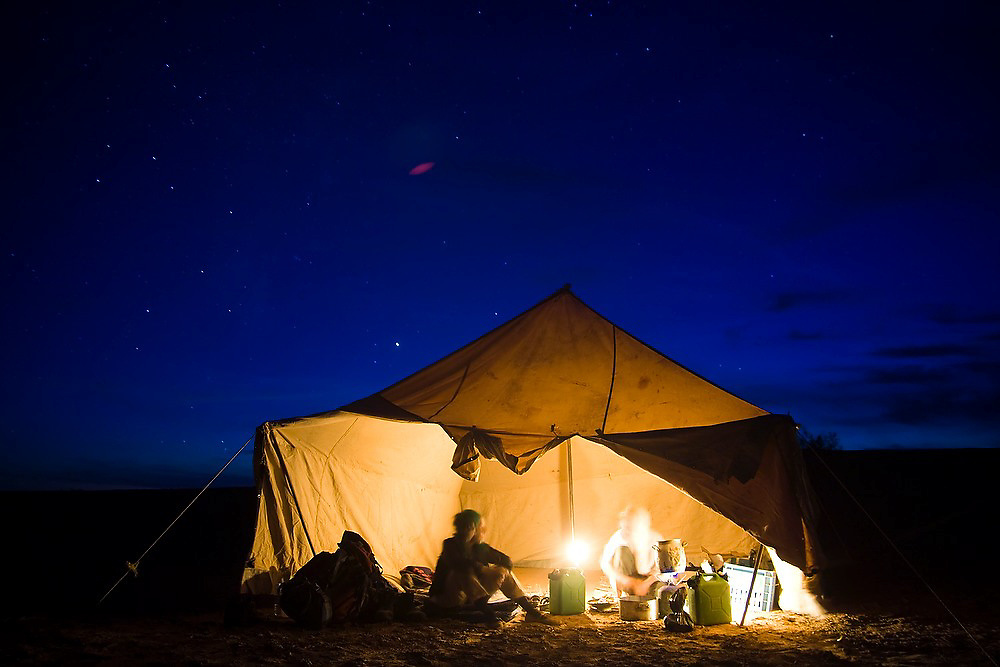 Nomad guide Elhussein Sbiti sits with American client Liana Welty in a tent at night on a three-day camel trek to the remote dunes of Erg Zehar, near M'hamid in the Moroccan Sahara.