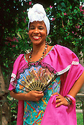 CUBA, HAVANA (HABANA VIEJA) Beautiful young lady in traditional  Cuban colonial garment with scarf and Spanish fan