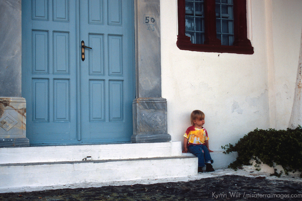 Europe, Mediterranean, Aegean, Greece, Greek Islands, Santorini, Thira. A young traveler rests on the step of a Santorini doorway.