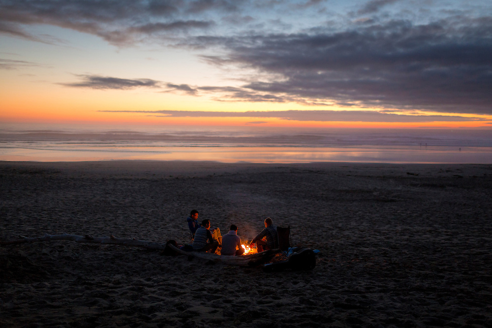 Friends watch the sunset around a campfire on South Beach, near Newport Oregon.