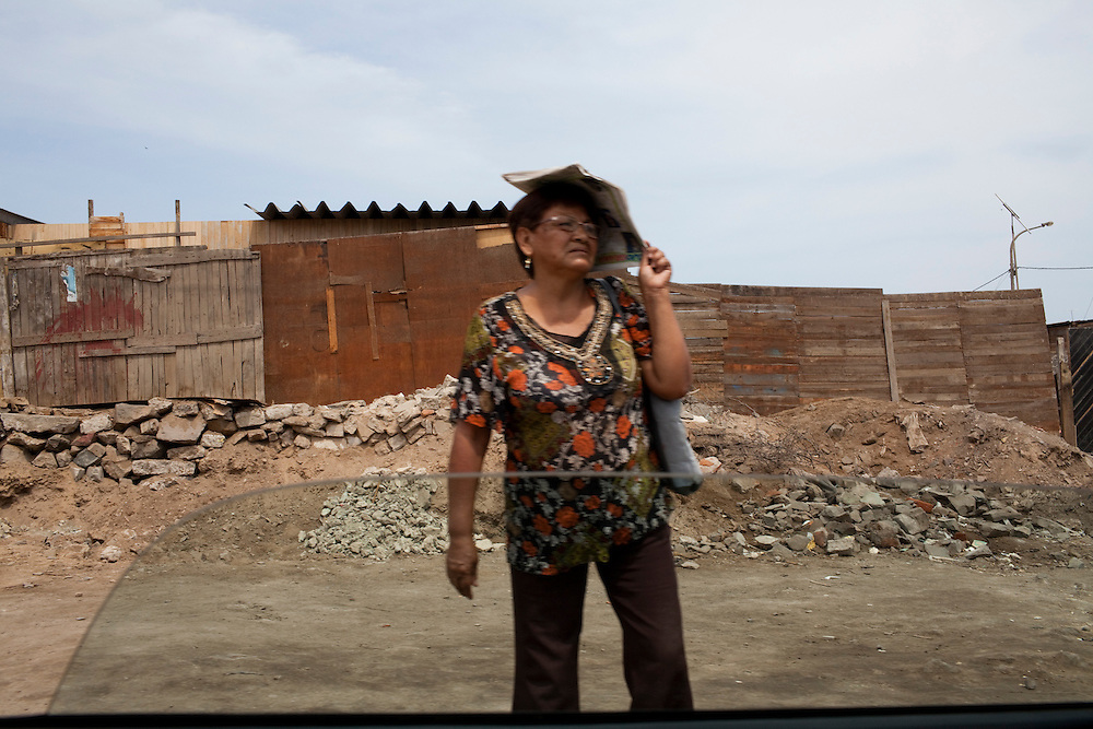 A woman stands on the side of the road on Monday, Apr. 13, 2009 in Ventanilla, Peru.