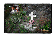 SHOT 2/6/15 5:26:59 PM - A roadside capilla in the mountains just outside of La Estancia, Mexico and featuring a cross as well as a small statue of Jesus. Roadside capillas, or tiny chapels, are common along the roads and highways of Mexico which is heavily Catholic and are often dedicated to certain patron saints or to the memory of a loved one that has passed away. Often times they contain prayer candles, pictures, personal artifacts or notes. (Photo by Marc Piscotty / © 2015)