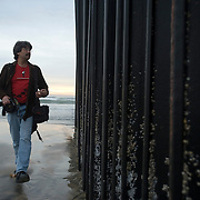 Tijuana Mexico ..photographer David Maung at the border fence in Playa Tijuana ..While working on this long term project 'La Frontera' I want to examine the cultural and humanitarian activities on both sides of a border that keeps the United States and Mexico apart with a wall of steel already 600 miles long. The turf wars of drug cartels, arms trafficking and rampant kidnappings turned cities like Tijuana into some of the most dangerous places on earth. Despite the violence many brave artists, photographers, architects, poets, humanitarians, teachers etc live and work in the shadow of the wall on both sides and have a positive influence on this region; they are the focus of my long term project along the border. (Over time I plan to cover the entire length from the Atlantic to the Pacific, these images were taken in and around Tijuana).© Stefan Falke