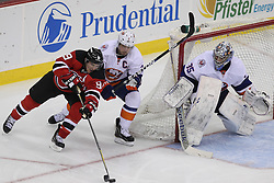 Apr 3; Newark, NJ, USA; New Jersey Devils left wing Zach Parise (9) skates with the puck towards New York Islanders goalie Al Montoya (35) while being defended by New York Islanders defenseman Mark Streit (2) during the third period at the Prudential Center.  The Devils defeated the Islanders 3-1.