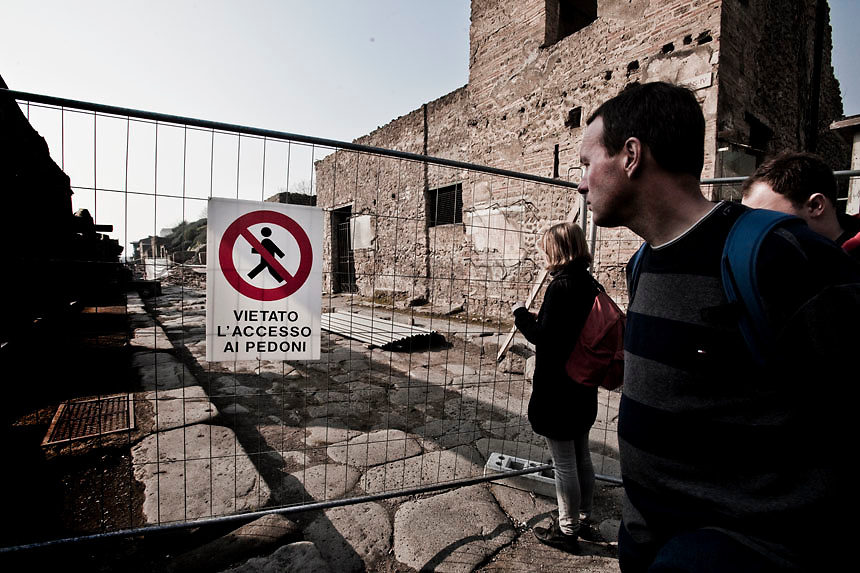 Tourists stands in front the collapsed areas of Pompeii.Nearly 4 month after the collapse of the House of the Gladiators and then of a wall at the House of the Moralist, Pompeii still faces neglet and mismanagement.Now the Italian government has begun to investigate the matter. Nine people are to be questioned, although Marcello Fiori, the emergency commissioner who was appointed to save the site in 2008, is conspicuously absent from the group.Those who will be grilled by the public prosecutor include the former superintendent of Naples and Pompeii, the site director who oversaw the waterproofing of the House of the Gladiators, the head of technical services at Pompeii, and an architect. The investigation will also examine Fiori's administration, which ended in July, including its use of government funds, which many critics have seen as wasteful and ineffective.