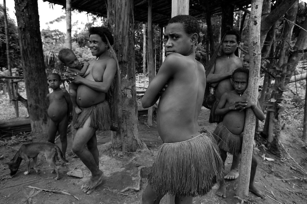 a family of the kombai tribe beneath their treehouse home, the womens grass skirts can be clearly seen.