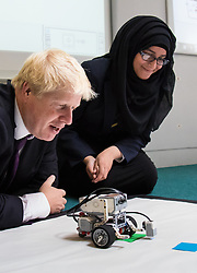 thoroughly absorbed Boris Johnson watches a robot programmed by students as it detects colour patches.
