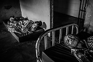 BARQUISIMETO, VENEZUELA - JULY 28, 2016: Patients José Rojas (left) and José Herrera (right) rest in their shared hospital room.  Rojas suffers from psychosis and mental retardation. He only has one eye and can barely walk. Herrera is diagnosed with senile dementia, and was abandoned by his family, living in the streets before a nonprofit organization found him and brought him to El Pampero.  The economic crisis that has left Venezuela with little hard currency has also severely affected its public health system, crippling hospitals like El Pampero Psychiatric Hospital by leaving it without the resources it needs to take care of patients living there, the majority of whom have been abandoned by their families and rely completely on the state to meet their basic needs. PHOTO: Meridith Kohut for The New York Time