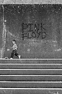 Young Boy running past some Graffiti on a Wall, Somerset, England.