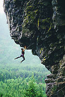 Rock climber hanging from overhanging rock.