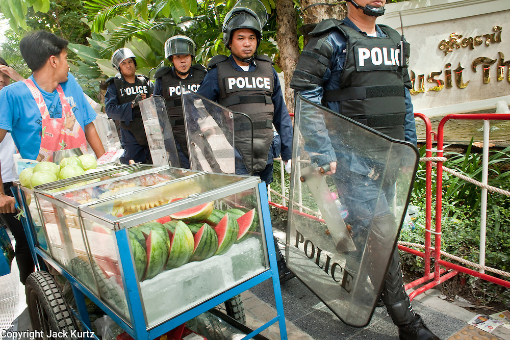 Apr. 19 2010 - BANGKOK, THAILAND: A fruit vendor makes room for Thai riot police to pass him in the Silom financial district in Bangkok Monday. Hundreds of Thai soldiers, including reservists and front line units, and riot police moved into the Silom financial district Monday, not far from the red-shirts' main protest rally site, in Ratchaprasong. The heavy show of force is to prevent the Red Shirts from entering the Silom area. Many of soldiers were greeted as heros by workers in the area, who oppose the Red Shirts.   Photo by Jack Kurtz