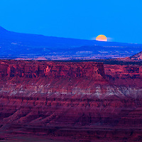 The full moon rises behind the La Sal mountains, over red rock cliffs in the Colorado River Plateau as seen from Dead Horse Point State Park near Moab, Utah. WATERMARKS WILL NOT APPEAR ON PRINTS OR LICENSED IMAGES.