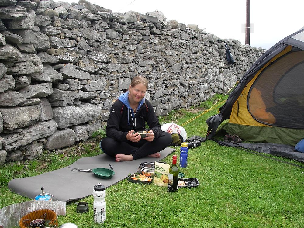Girl eating outside tent, Ireland..................