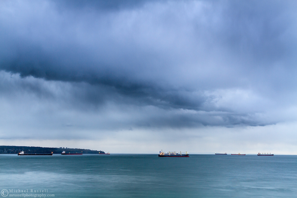 A rainstorm heads towards Stanley Park over the Tankers at English Bay in Vancouver, British Columbia, Canada