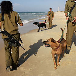 Israeli soldiers walk their guard dogs on the beach near Elei Sinai, a northern Jewish settlement, Gaza, Palestinian Territories, Nov. 6, 2004. Israel's parliament recently supported compensation payments for Jewish settlers leaving the Gaza Strip, in a vital vote for Prime Minister Ariel Sharon's plan to evacuate the occupied territory.