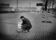 Indigent man warms himself by lighting a fire with plastic wrappers and crumpled paper at dusk, Wuhai, Inner Mongolia, China.