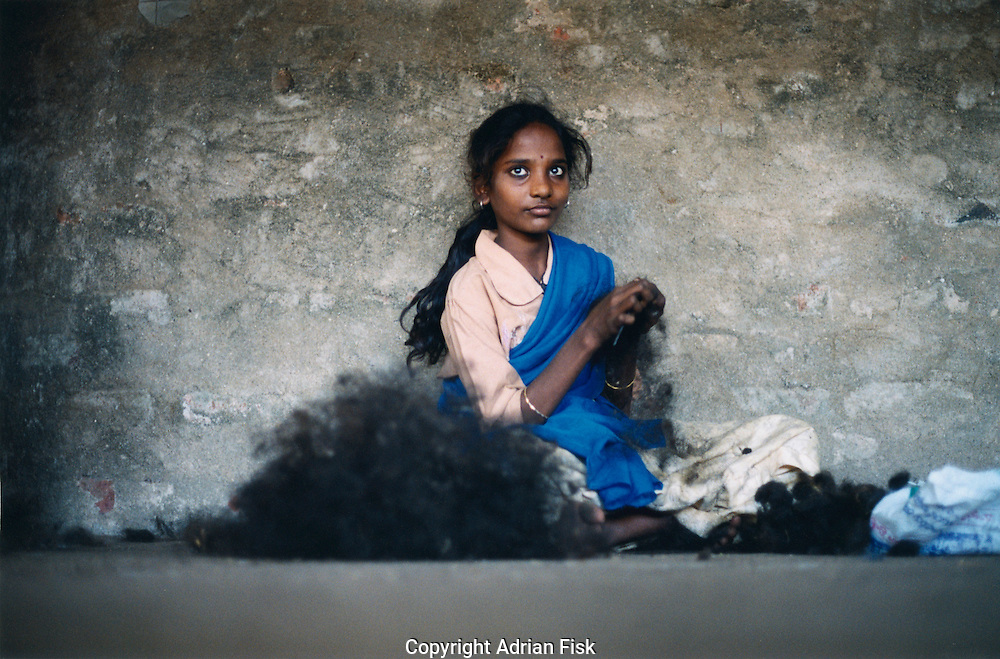In the town of Eleru in the state of Andhra Pradesh a young girl works at untangling village hair. Village hair often arrives full of dirt and knots, because of their small and nimble fingers children often get the labourious and difficult job of sorting this hair.