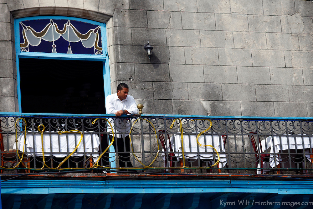 Central America, Cuba, Havana. Waiter watches street from balcony.