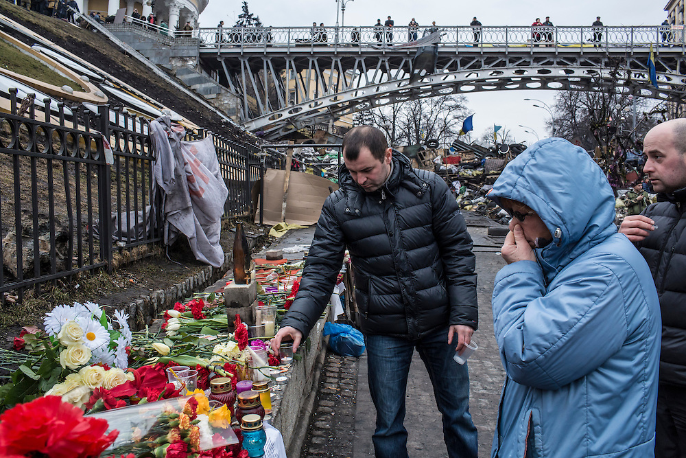KIEV, UKRAINE - FEBRUARY 23: A man places flowers at a memorial to anti-government protesters killed in chashes with police on Independence Square on February 23, 2014 in Kiev, Ukraine. After a chaotic and violent week, Viktor Yanukovych has been ousted as President as the Ukrainian parliament moves forward with scheduling new elections and establishing a caretaker government. (Photo by Brendan Hoffman/Getty Images) *** Local Caption ***