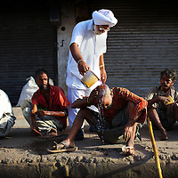 A homeless man gets help from a volunteer with the Bhai Daya Singh Charitable Trust in Delhi, India.