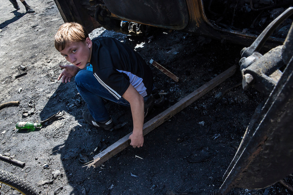 MARIUPOL, UKRAINE - MAY 10: A boy looks at debris scattered around a burned tank a day after deadly clashes on May 10, 2014 in Mariupol, Ukraine. A referendum on greater autonomy is planned for the region tomorrow. (Photo by Brendan Hoffman/Getty Images) *** Local Caption ***