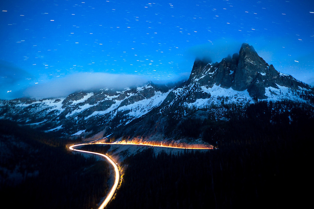 Cars drive Highway 20 at night over Washington Pass, below Liberty Bell and the Early Winter Spires, North Cascades Scenic Highway Corridor, Washington.