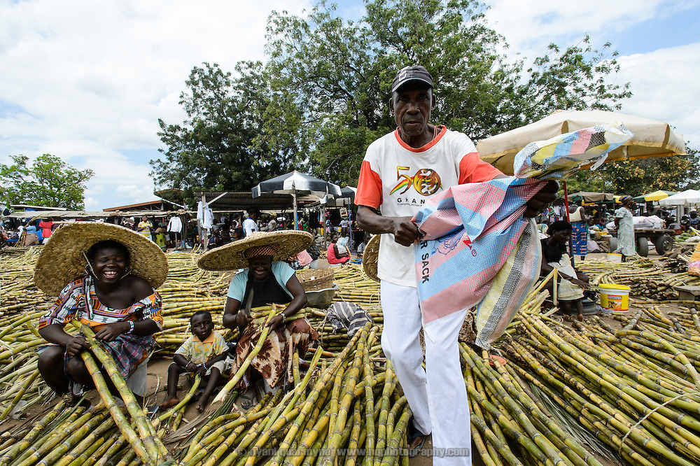 A man buying sugarcane clowns for the camera at a market in Dabala Junction in the Volta Region of Ghana.