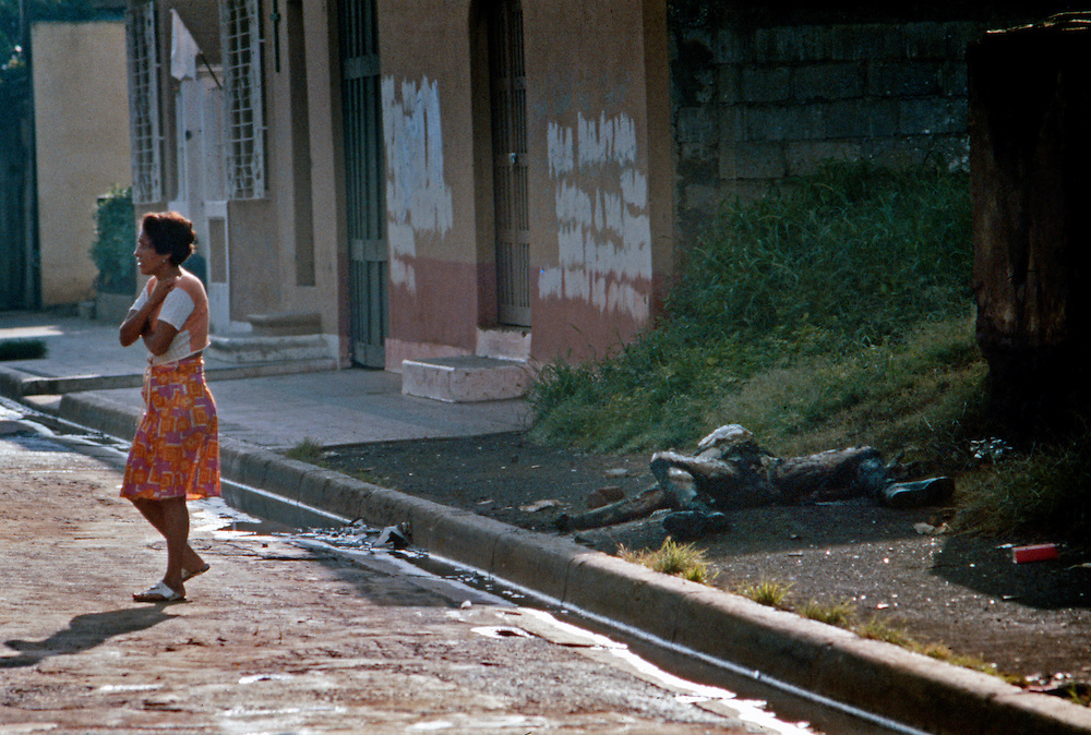 A woman passes the burned and charred body of a Nicaragua National Guardsman after house to house street fighting in Civil War in Nicaragua - 1978.
