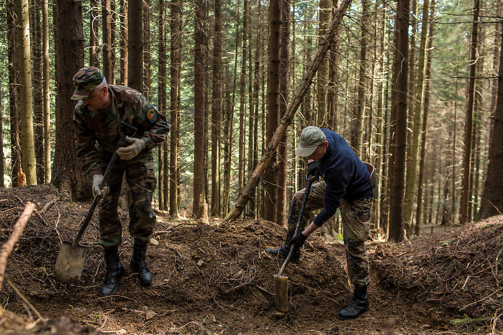 SKOLE, UKRAINE - MAY 1, 2015: Volodymyr Kharchuk, left, and Ostap Kozak, deputy director and archivist of the organization Dolya, respectively, dig at a World War II-era mass grave believed to contain the remains of Ukrainian partisans in Skole, Ukraine. Dolya was formed to excavate and repatriate remains from World War II, though its focus is often on locating the graves of Ukrainian partisans killed by Soviet forces. CREDIT: Brendan Hoffman for The New York Times