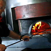 SHOT 2/16/11 4:29:01 PM - Marco's Coal Fired Pizza owner Mark Dym works the coal fired oven at the downtown Denver, Co. location. The downtown Denver restaurant is passionate about using only the finest, most authentic ingredients available: including Antimo Caputo 00 flour from a third-generation family mill, artisanal cheeses imported from the Italian countryside and fresh, locally grown produce found right here in Colorado. Marco's Coal-Fired Pizza is certified as an authentic Neapolitan restaurant by the Verace Pizza Napoletana - the only certified restaurant in Colorado, and one of only 40 in the USA. (Photo by Marc Piscotty / © 2011)