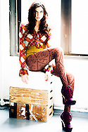 Editorial shot of model sitting on apple-boxes at window