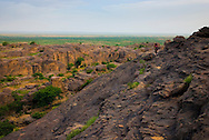 A shepherd walks on the bandiagara Escarpment following his flock of goats. The Dogon Country is the most visited part of Mali with tourists visiting its tipical  villages that can be located on the cliff, on the sandy plain or in the rocky plateau