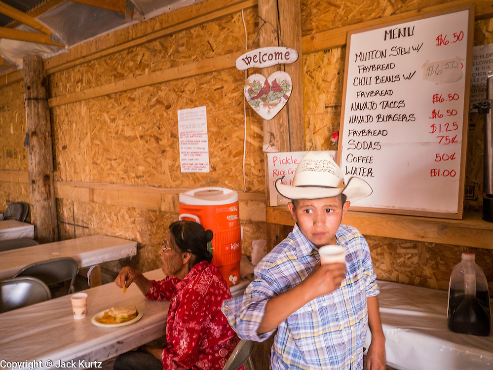 """13 JULY 2012 - FT DEFIANCE, AZ: A boy drinks an iced tea in the chow hall at the 23rd annual Navajo Nation Camp Meeting in Ft. Defiance, north of Window Rock, AZ, on the Navajo reservation. Preachers from across the Navajo Nation, and the western US, come to Navajo Nation Camp Meeting to preach an evangelical form of Christianity. Evangelical Christians make up a growing part of the reservation - there are now more than a hundred camp meetings and tent revivals on the reservation every year. The camp meeting in Ft. Defiance draws nearly 200 people each night of its six day run. Many of the attendees convert to evangelical Christianity from traditional Navajo beliefs, Catholicism or Mormonism. """"Camp meetings"""" are a form of Protestant Christian religious services originating in Britain and once common in rural parts of the United States. People would travel a great distance to a particular site to camp out, listen to itinerant preachers, and pray. This suited the rural life, before cars and highways were common, because rural areas often lacked traditional churches. PHOTO BY JACK KURTZ"""
