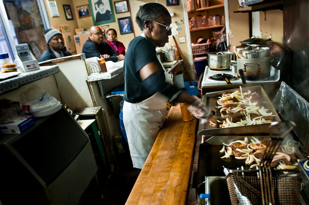 "Miss Ann frying burgers...Ann's Snack Bar in the Atlanta neighborhood Kirkwood..The small restaurant is owned and operated by Ann Price, known to patrons as ""Miss Ann"" and has been in operation since 1973.  The house special is called the ""Ghetto Burger"", a double bacon chili cheeseburger with a secret ingredient.Wall Street Journal named the Ghetto Burger the best hamburger in America."