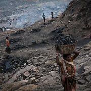 Local villagers dig out coal from the open cast mines and carry them back to their village in Borapahari in Jharia, Jharkhand, India.  Photo: Sanjit Das