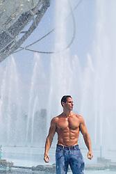 muscular bodybuilder in an outdoor fountain