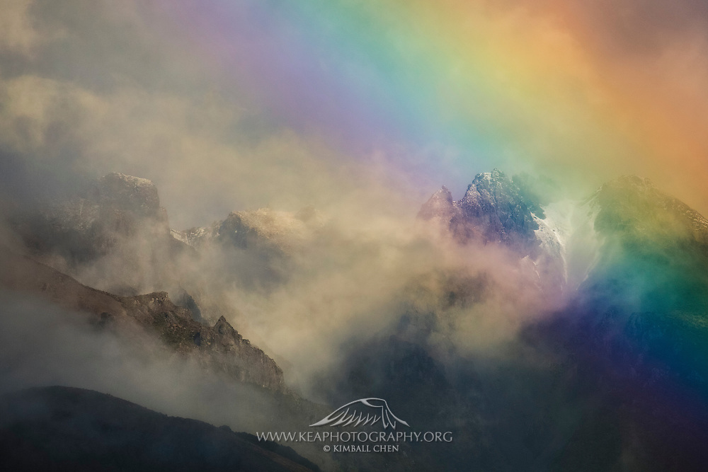 A rainbow graces the Takitimu Mountains in Southland, New Zealand.  Fog and mist rapidly dissipate as two weeks of rain & clouds finally ease.