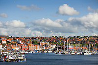 Whitby harbour seen in late evening sunshine, to the left of the images many new houses have been built on the site of the former shipyard.
