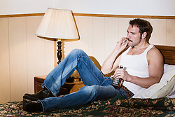 man smoking in a cheap motel bed with a bottle of Jack Daniels in hand