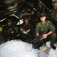 Members of a special Colombian anti-narcotics unit proudly pose for the press in front of a pile of cocaine in a drug lab that the police discovered in the jungle near Caucasi, about 250 miles north of Bogota. Colombia is the leading producer of cocaine in the world and most of the drug trade is controlled by armed groups who derive their funding from drug trafficking. The lab and all the cocaine found in it, an estimated 2.5 tons, was destroyed with explosives.(Photo/Scott Dalton)