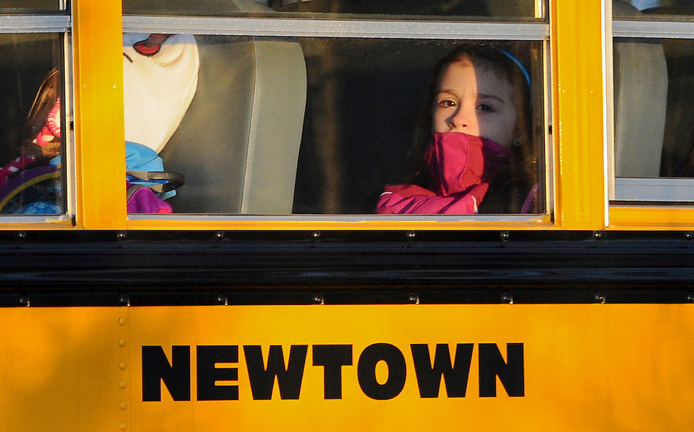 A girl sits on a Newtown bus leaving the new Sandy Hook Elementary School after the first day of classes in Monroe, Conn., Thursday, Jan. 3, 2013.  The Sandy Hook students started today in a new school, formerly called Chalk Hill School in Monroe.  It was renamed Sandy Hook Elementary and overhauled especially for the students from the Sandy Hook School shooting. (AP Photo/Jessica Hill)