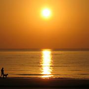 Man walking his dog at sunrise on Jekyll Island Beach.
