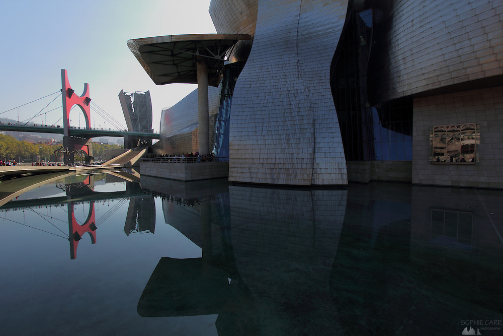 A view of the north side of the Guggenheim museum in Bilbao, with the red-painted suspension of the Puente de la Salve