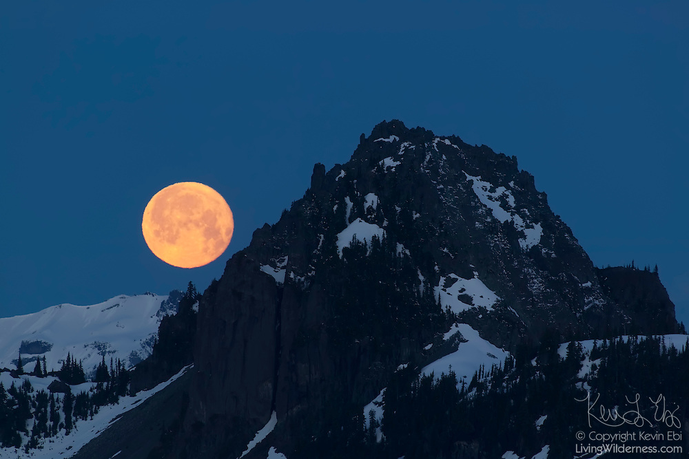 The full moon sets behind Seymour Peak, located just east of Mount Rainier. This scene was captured from near Chinook Pass, Washington.