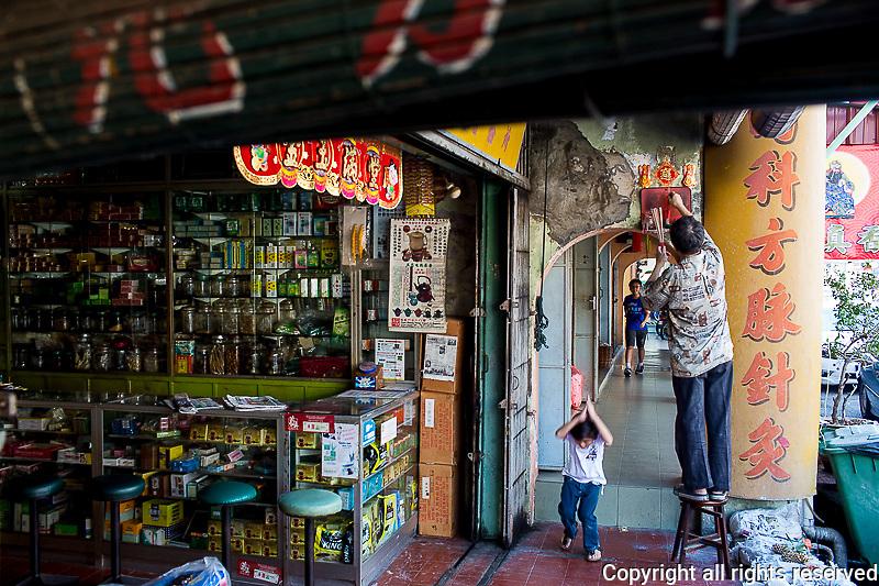 tending to an ancestor shrine in 5 foot way along Kimberley Street near Penang Road