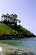 Man on the beach in Lagoa Azul (Blue lagoon) with baobab trees on a hill. Lagoa Azul is on the north coast of Sao Tome island.