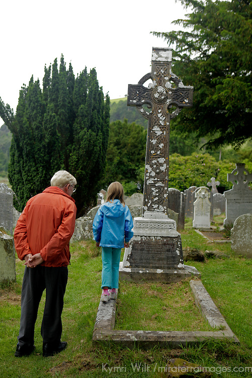 Europe, Ireland, Glendalough. A young girl expores the cemetary at Glendalough with her Grandfather.