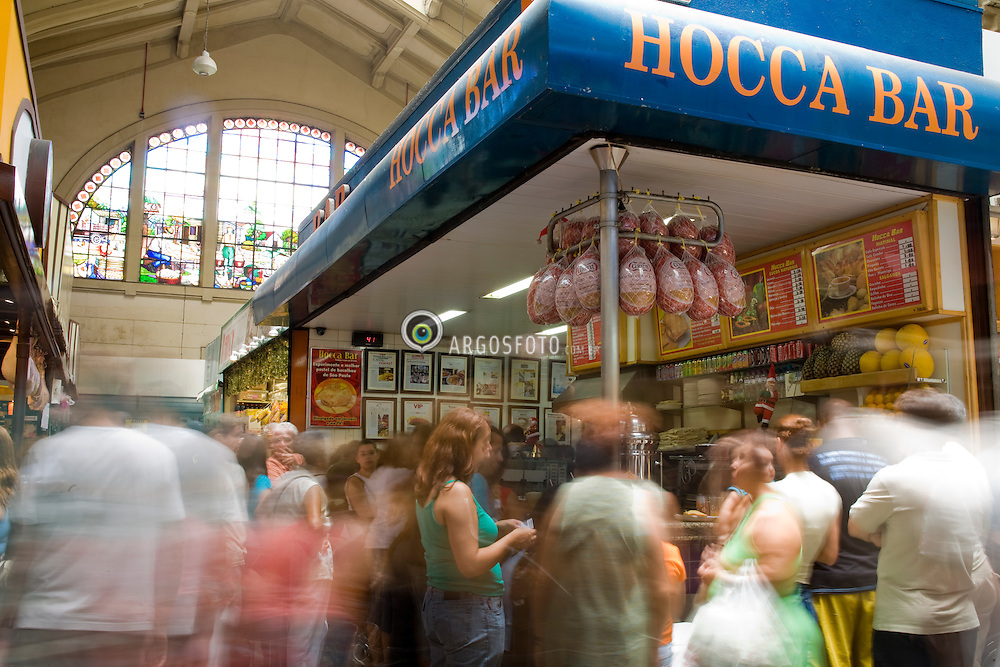 O Mercado Municipal de Sao Paulo, inaugurado em 1933, eh um importante entreposto comercial de atacado e varejo, especializado na comercializacao de produtos alimenticios. Reformado em 2004, o mercado ganhou quiosques de bares e restaurantes, firmando-se como importante atracao turistica da cidade. O Hocca Bar oferece o mais famoso petisco do mercado, o pastel de bacalhau / The Municipal Market of Sao Paulo, called Mercadao, in Downtown Sao Paulo, is an impressive building in the neoclassical style, measuring over 22 thousand square meters in area, tastefully outfitted and boasting a collection of beautiful stained glass windows.  The market is also famous for pastéis de bacalhau, fried pastry pockets stuffed with salt cod. One of the best can be found at Hocca Bar
