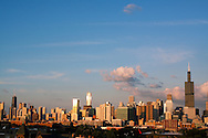 The late evening sun reflects off the many tall buildings that make up the famous Chicago skyline.